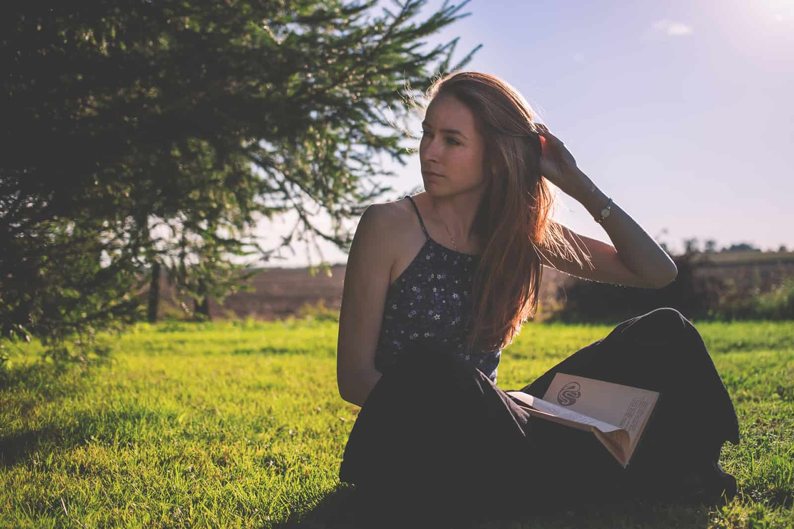 eine nachdenkliche Frau, die beiseite schaut, während sie ein Buch hält und auf dem Gras sitzt