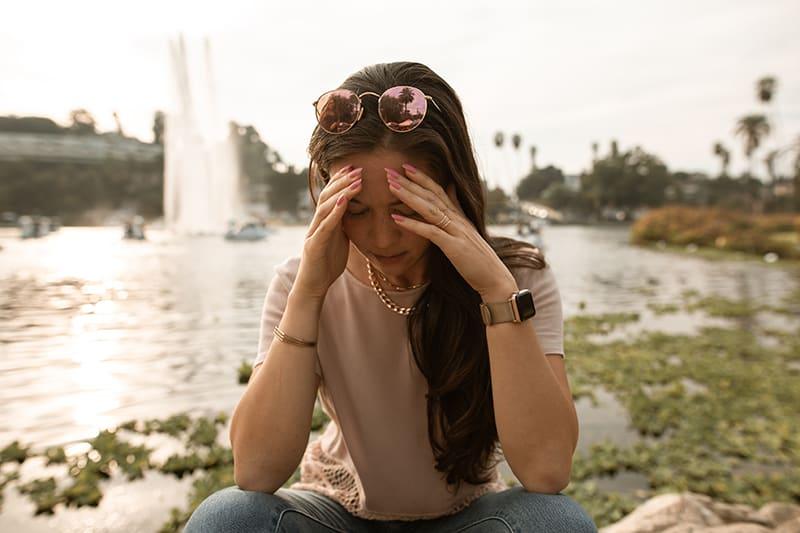eine nachdenkliche Frau, die die Stirn berührt, während sie in der Nähe des Sees sitzt
