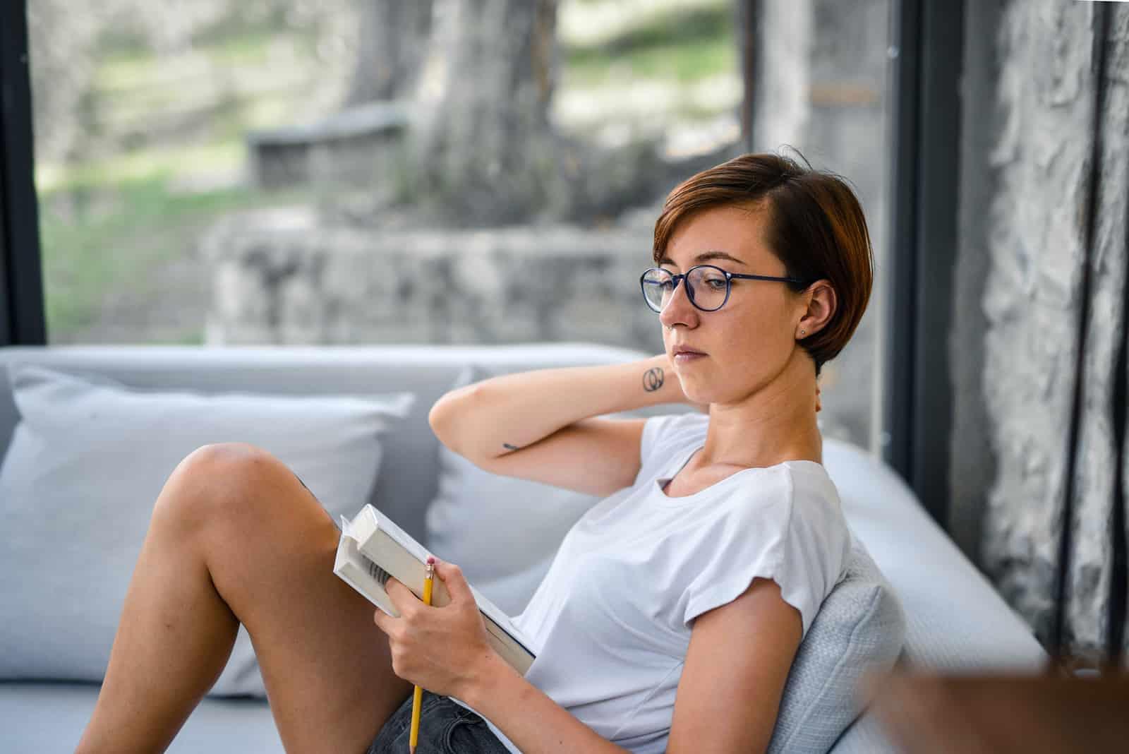 eine nachdenkliche Frau, die ein Buch hält, während sie auf dem Sofa sitzt