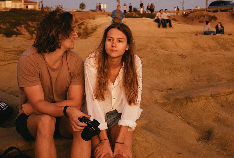 eine nachdenkliche Frau, die neben einem Mann auf einem Felsen sitzt, während er sie ansieht