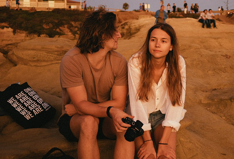 eine nachdenkliche Frau, die neben ihrer Freundin auf dem Felsen sitzt und sie ansieht