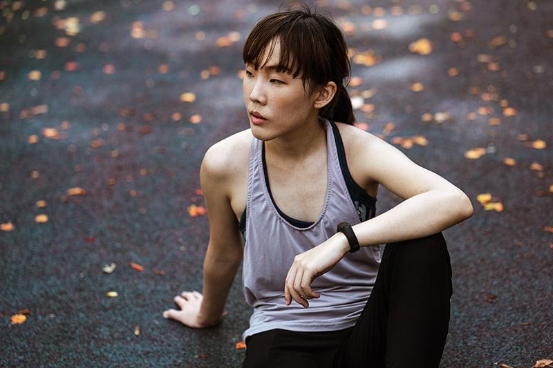 eine nachdenkliche Frau in Sportbekleidung, die auf der Straße sitzt und zur Seite schaut
