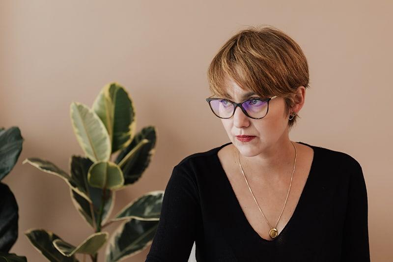 eine nachdenkliche Frau mit Brille, die zur Seite schaut