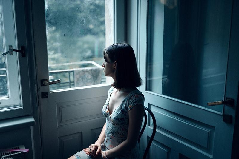eine nachdenkliche Frau, die auf dem Stuhl sitzt und durch das Fenster schaut