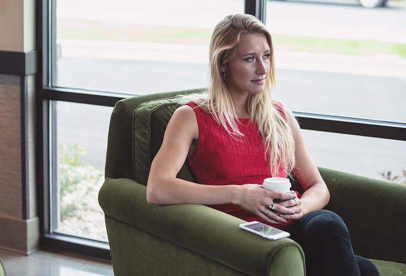 eine nachdenkliche Frau, die im Sessel sitzt und ihr Smartphone ignoriert