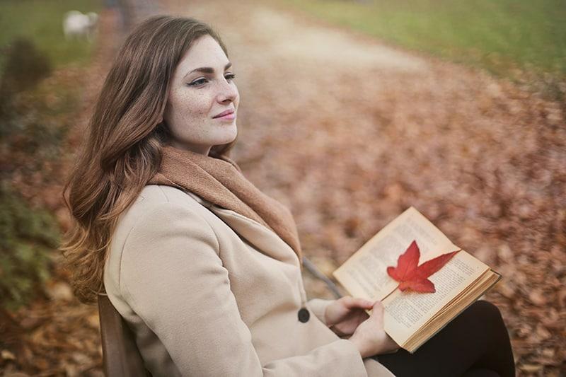 eine positive Frau, die denkt, während sie ein Buch hält und auf der Bank im Park sitzt