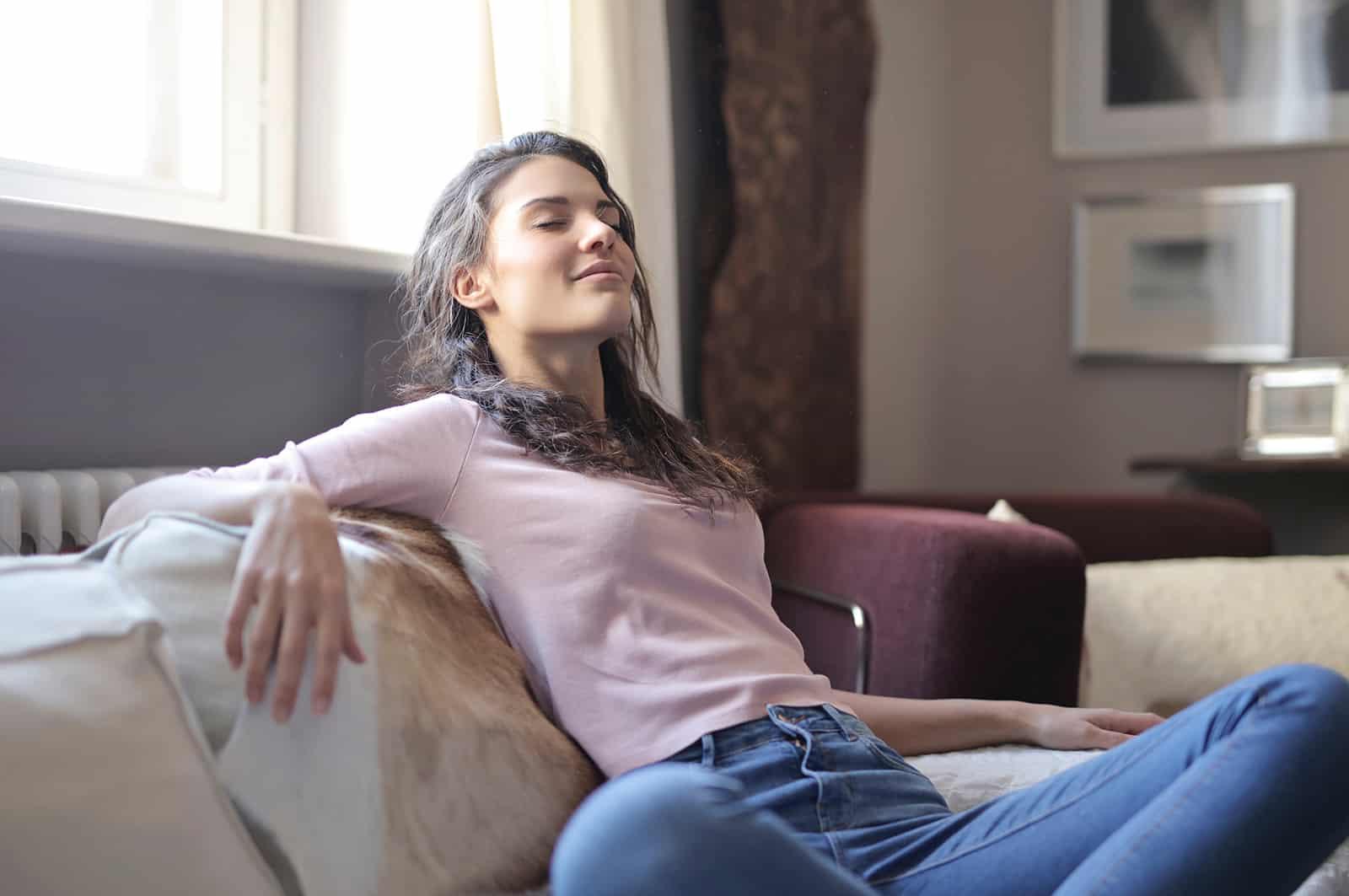 eine positive Frau, die mit geschlossenen Augen auf der Couch sitzt