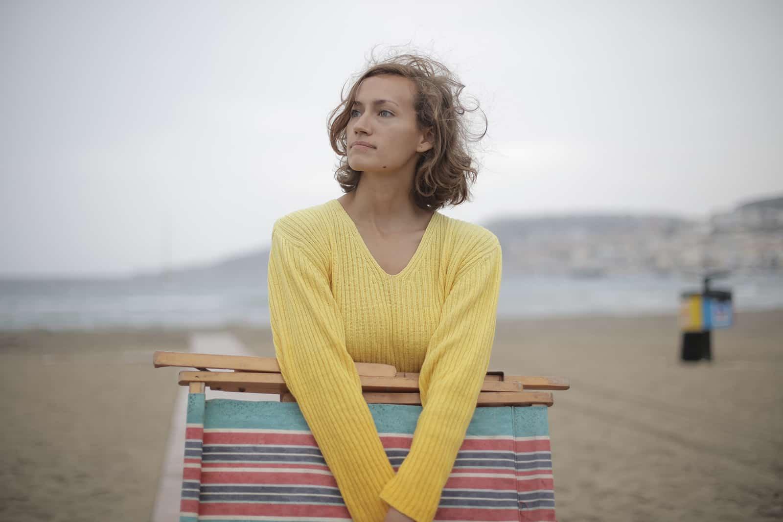eine ruhige Frau, die einen gefalteten Liegestuhl hält, während sie am Strand steht