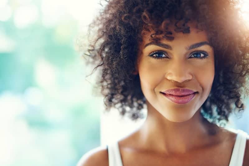 eine schöne junge schwarze Frau mit einem fröhlichen Gesichtsausdruck