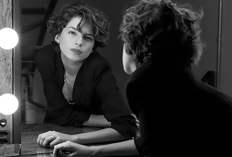 eine selbstbewusste Frau, die sich vor den Spiegel lehnte und sich selbst ansah