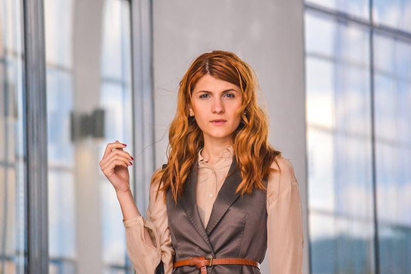 eine selbstbewusste Frau mit roten Haaren, die im Gebäude steht