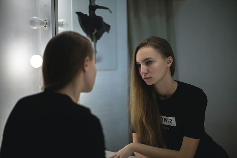 eine unsichere Frau, die beim Nachdenken vor dem Spiegel steht