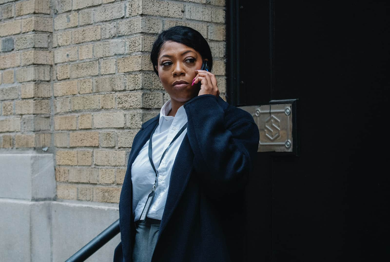 eine verärgerte Frau, die am Telefon spricht, während sie in der Nähe der Tür steht