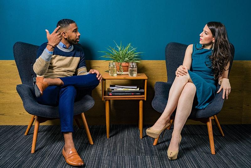 Eine verärgerte Frau hört einem Mann zu, der mit ihr spricht, während er zusammen in einer Lobby sitzt