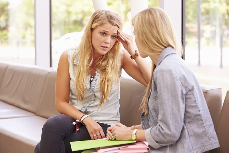 eine verärgerte Frau, die mit einer Freundin am Fenster sitzt