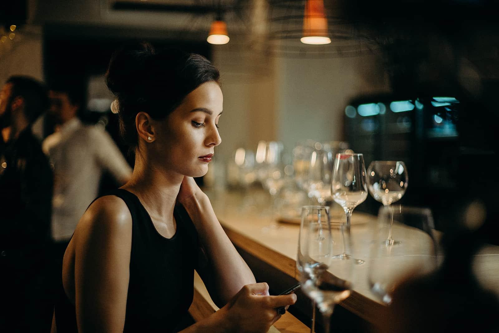 ernsthafte Frau SMS auf einem Smartphone sitzen allein an der Theke