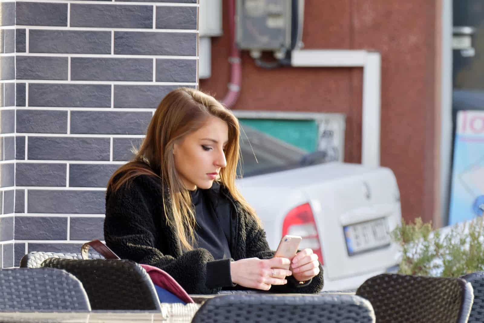 ernsthafte Frau, die ein Smartphone beim Sitzen im Café betrachtet