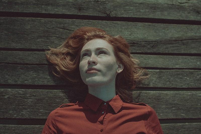 ernsthafte Frau, die auf dem Holzboden liegt und aufschaut