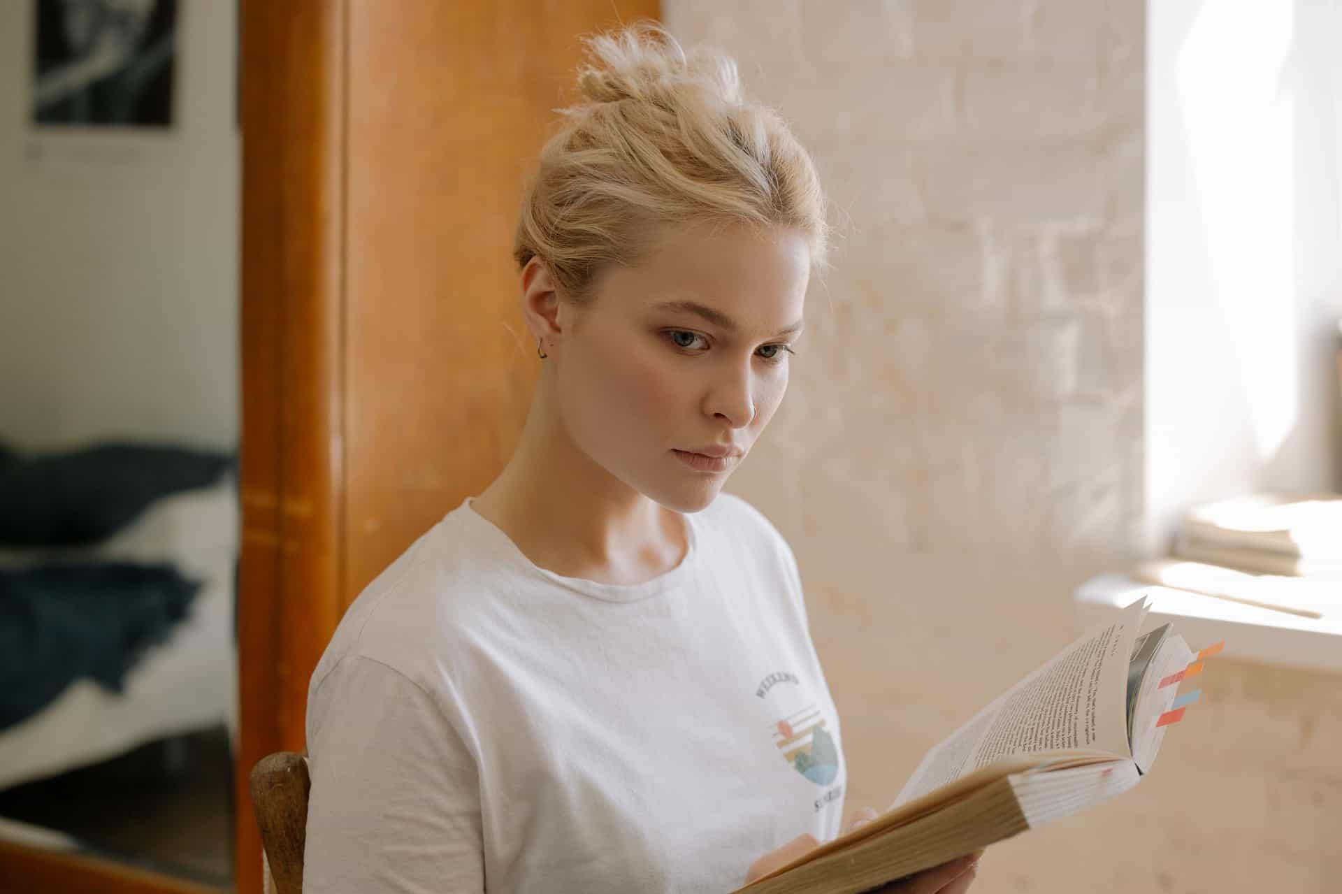 ernsthafte Frau, die ein Buch hält und zur Seite schaut