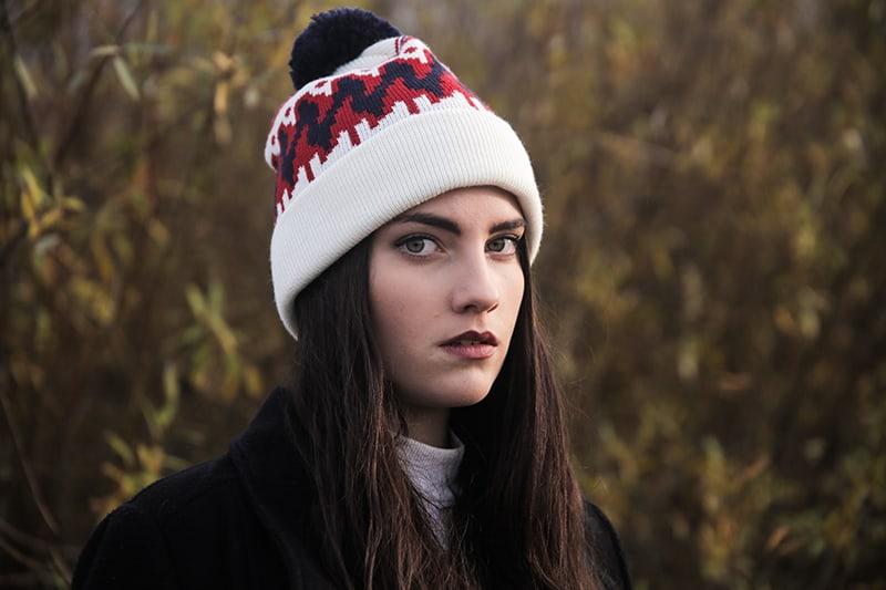 ernsthafte Frau, die eine Kappe trägt, die in einem Feld steht