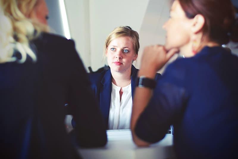ernsthafte Geschäftsfrau, die ihren zwei Kollegen beim Sitzen am Tisch zuhört