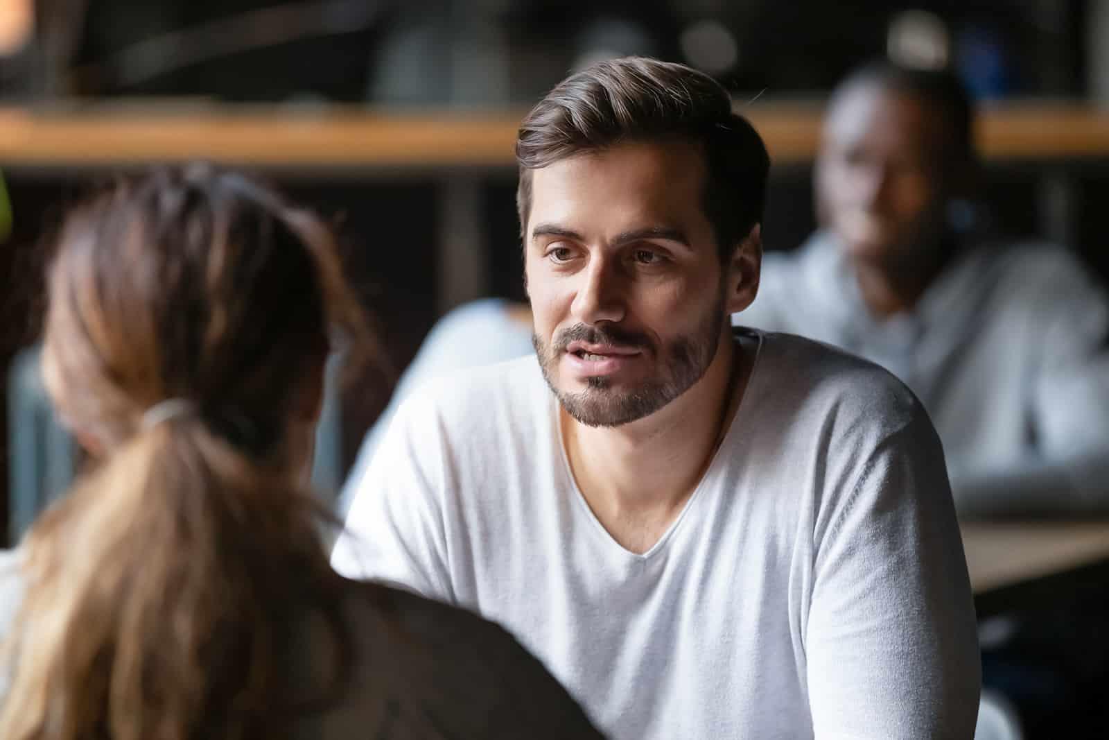 ernsthafter Mann, der ein Gespräch mit einer Frau hat, während er am Tisch sitzt