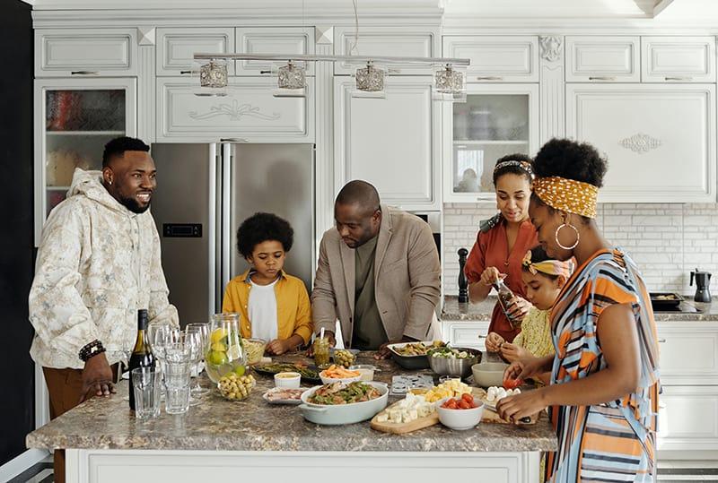 glückliche Familie, die Essen zusammen in der Küche zubereitet
