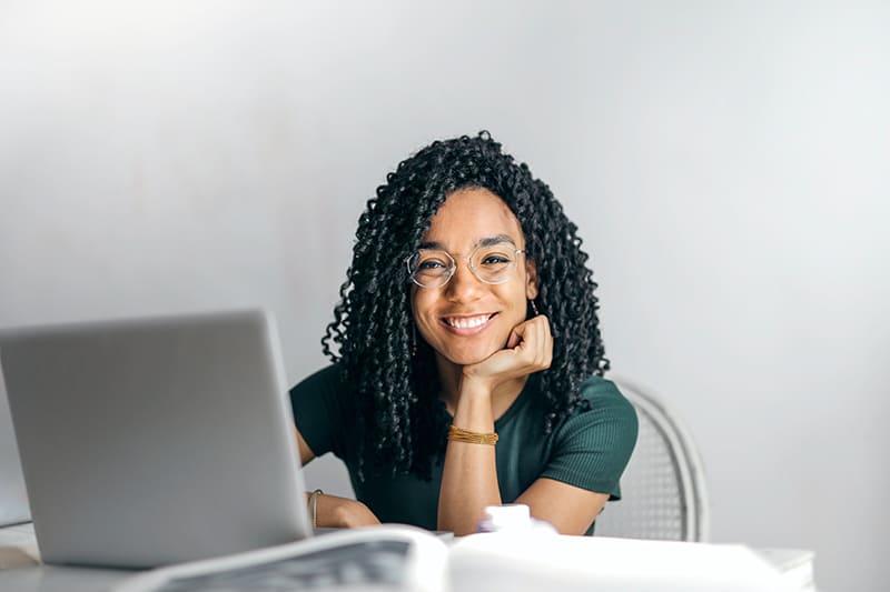 lächelnde Frau, die Kopf auf einer Hand lehnt, die vor dem Laptop sitzt
