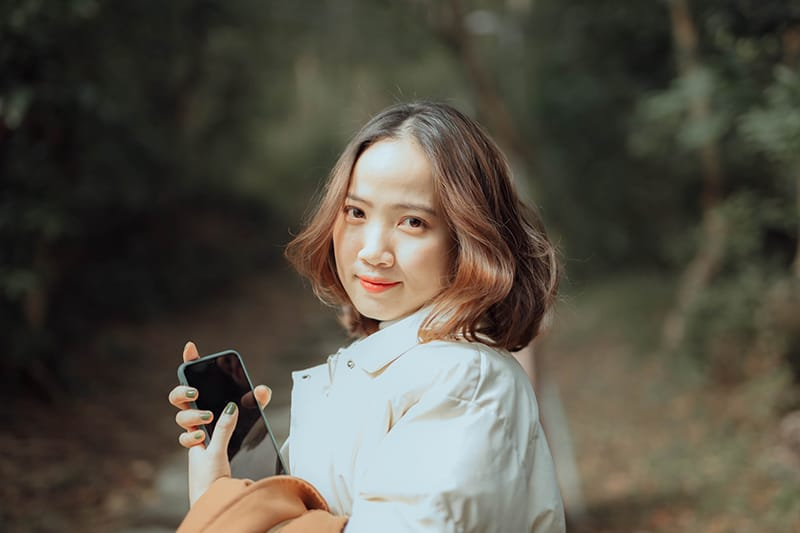 lächelnde Frau, die Smartphone hält, während sie im Park steht