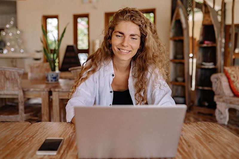 lächelnde Frau, die auf ihrem Laptop plaudert, während sie am Tisch sitzt