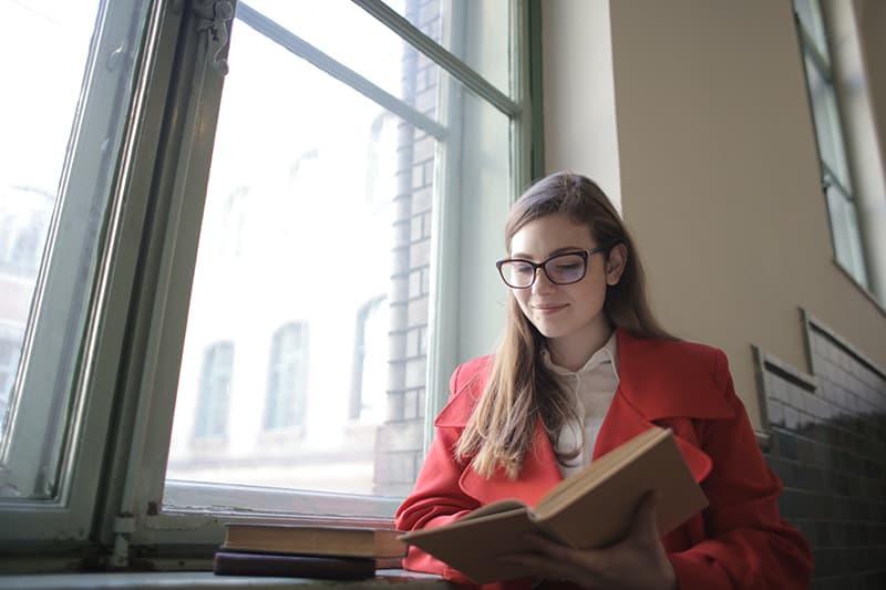 lächelnde Frau, die ein Buch liest, während sie nahe am Fenster steht