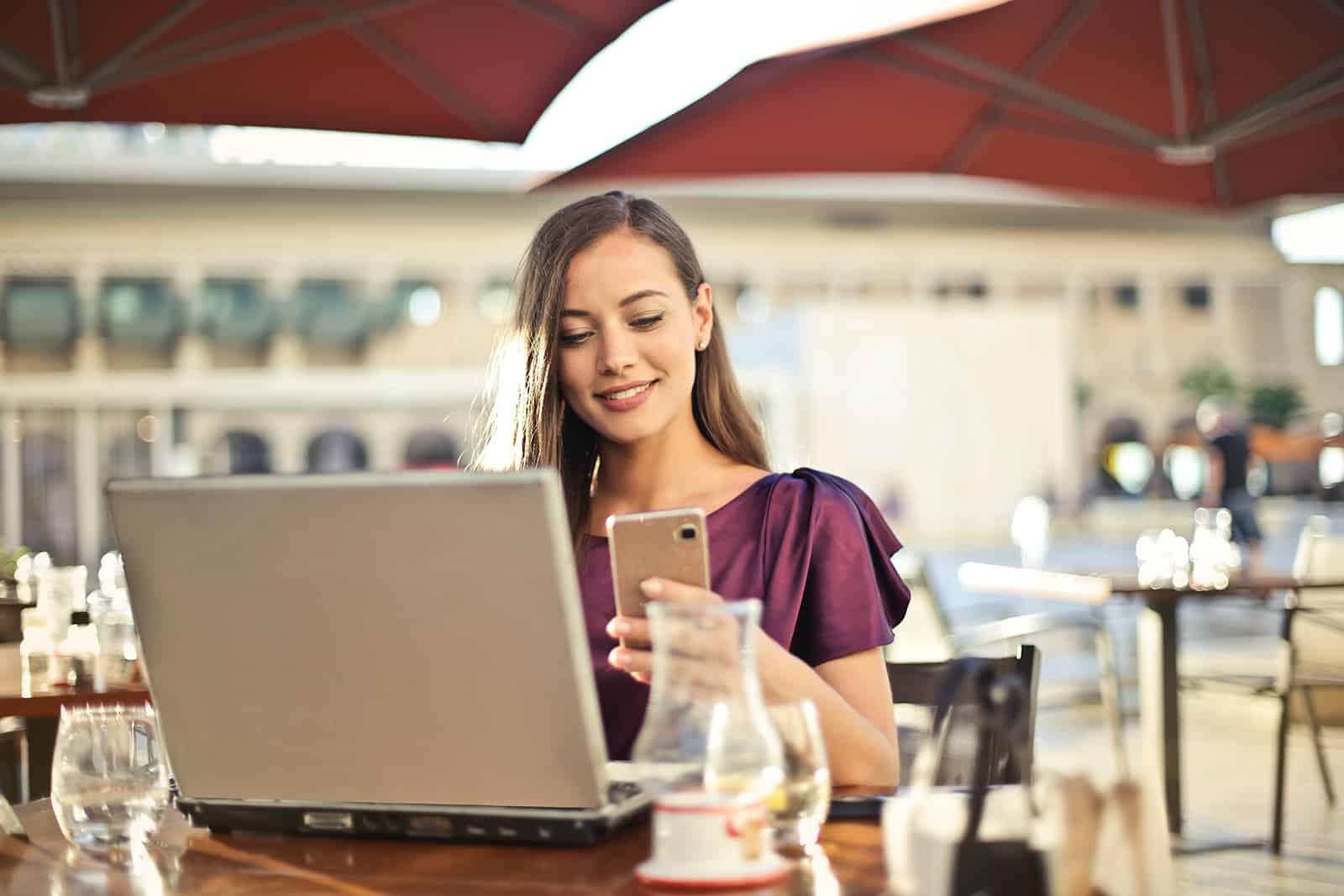 lächelnde Frau, die eine Nachricht auf ihrem Smartphone liest, das im Café sitzt