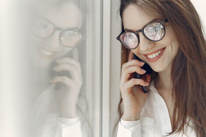 lächelnde Frau, die einen Anruf hat, während sie in der Nähe des Fensters steht