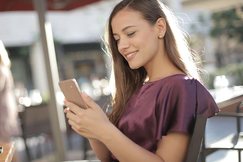 lächelnde Frau, die ihr Smartphone beim Sitzen im Café betrachtet