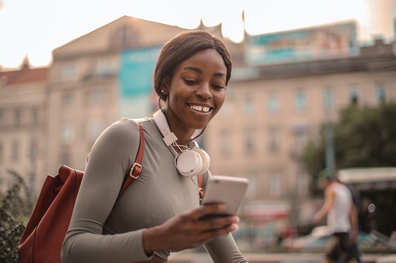 lächelnde Frau, die ihr Smartphone beim Gehen in der Stadt betrachtet