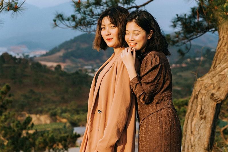 lächelnde Frau, die ihre Freundin von hinten umarmt, während sie in der Nähe des Baumes steht