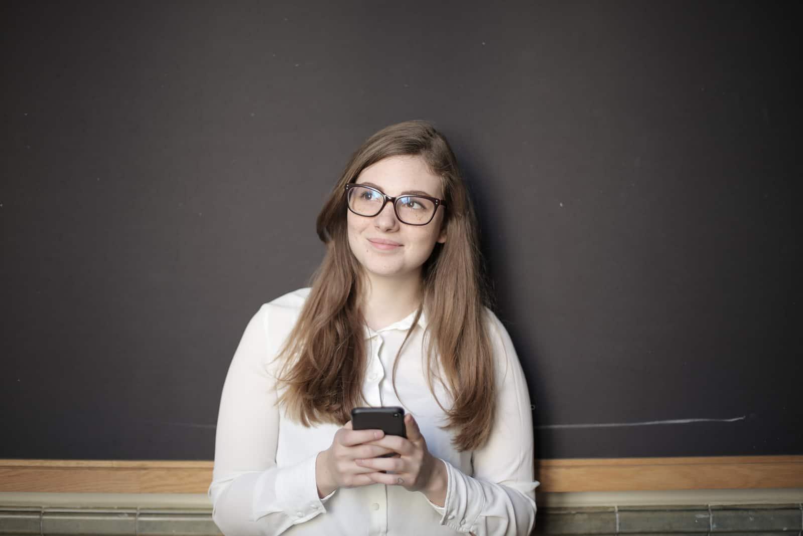 lächelnde Frau, die mit einem Smartphone hält und beiseite schaut