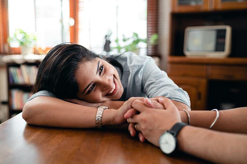 lächelnde Frau, die sich auf den Tisch stützt und die Hand ihres Partners hält