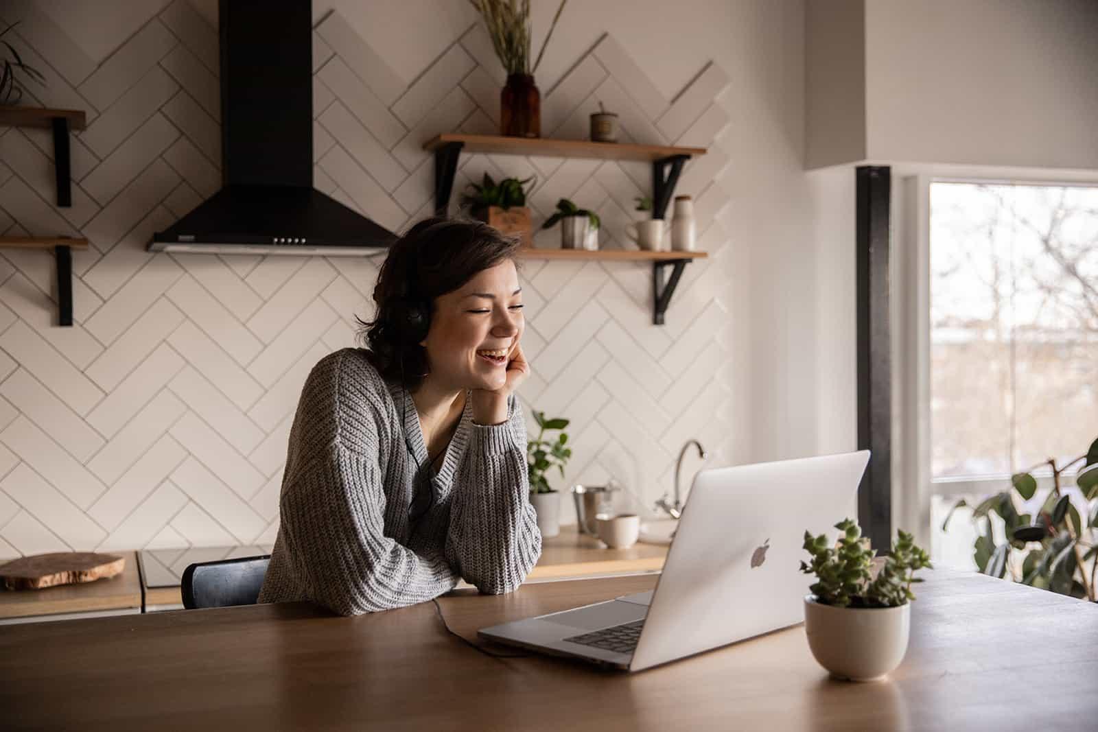 lächelnde Frau, die über Laptop in der Küche spricht