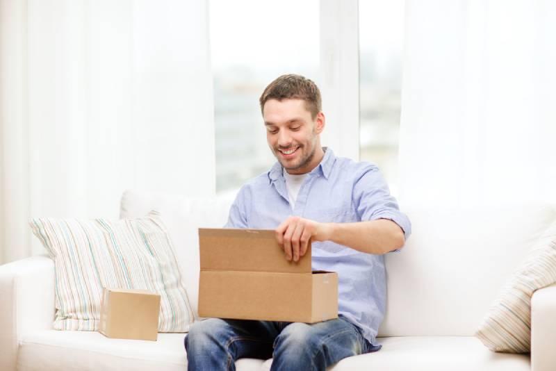 lächelnder Mann, der Pappkartons öffnet