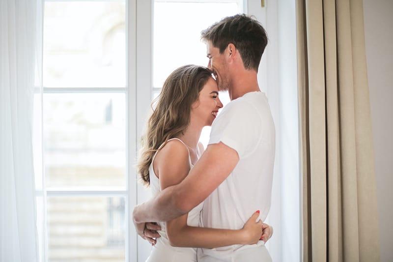 lächelndes Paar, das sich umarmt und neben dem Fenster steht