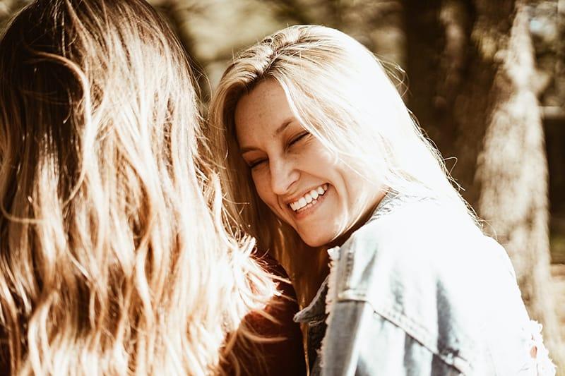 lachende Frau mit blonden Haaren, die ihre Freundin ansieht