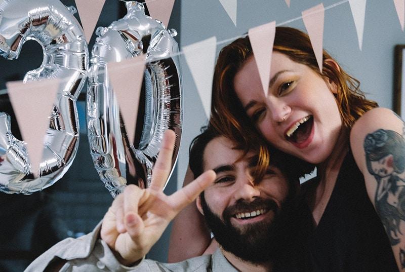 lachender Mann und eine Frau, die sich auf einer Geburtstagsfeier umarmen