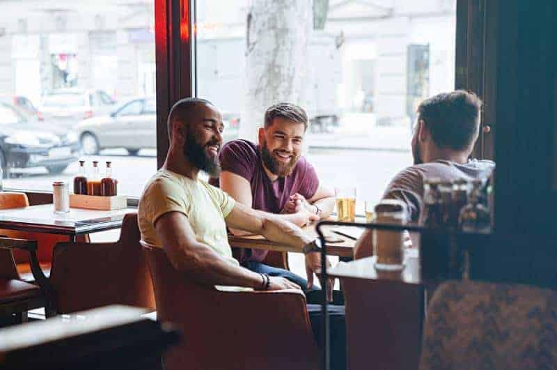 männliche Freunde, die in der Kneipe sprechen