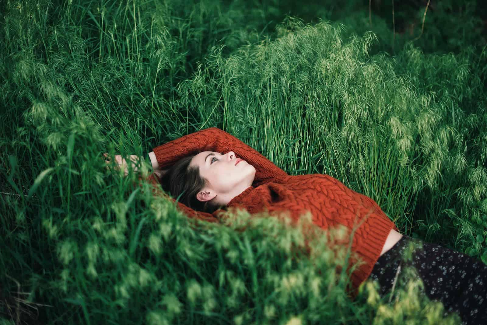 nachdenkliche Frau, die auf einer Wiese liegt und aufschaut