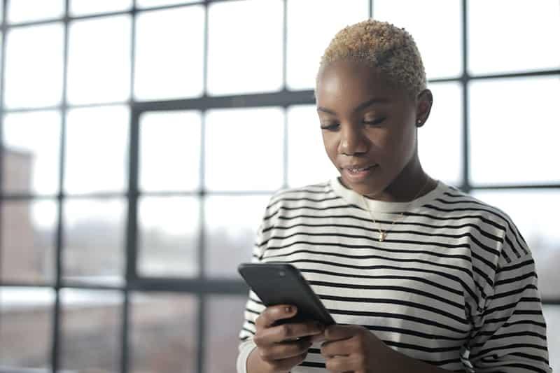 nachdenkliche Frau mit einem Smartphone beim Stehen neben dem Fenster