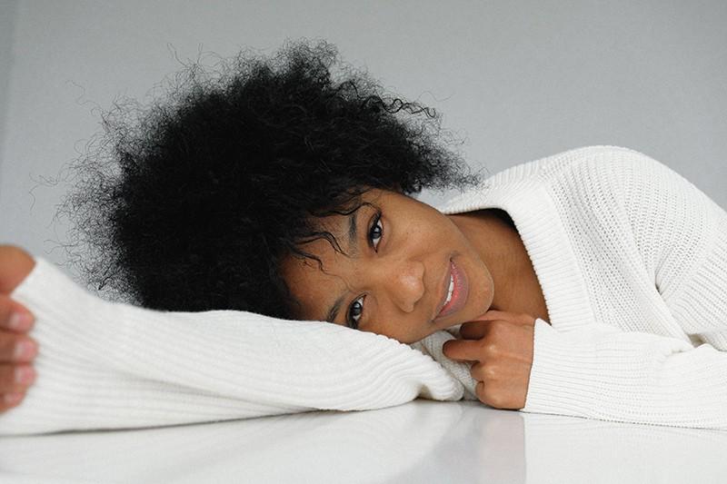 natürliche Schönheit Frau im weißen Pullover, der sich auf den Tisch stützt