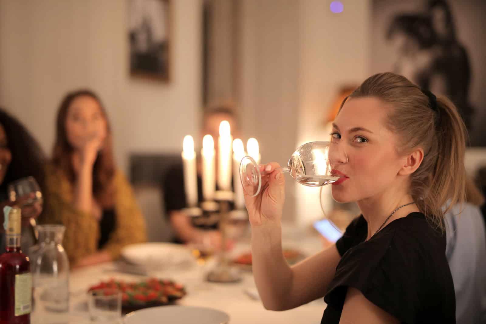 positive Frau, die Wein während eines Abendessens mit Freunden trinkt