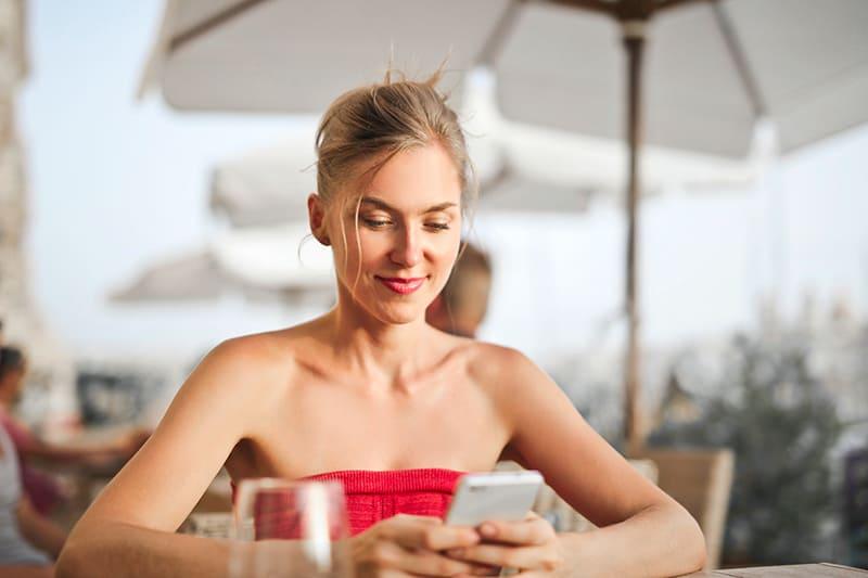 positive Frau, die ihr Smartphone beim Sitzen im Café betrachtet