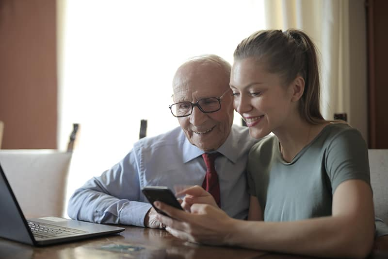 positive Frau, die einem älteren Mann zeigt, wie man ein Smartphone benutzt, während man am Tisch sitzt